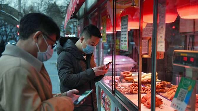 Người dân Bắc Kinh đeo khẩu trang khi mua sắm bên ngoài.