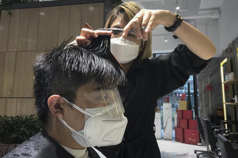 Cả thợ cắt tóc và khách hàng đều đeo khẩu trang nhằm tránh lây nhiễm bệnh.
