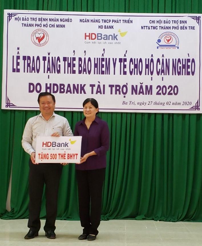 Bà Ca Thị Lắm - Chủ tịch chi hội bảo trợ bệnh nhân nghèo huyện Ba Tri, đại diện bà con nhận biểu trưng trao tặng thẻ BHYT. Ảnh: HD Bank
