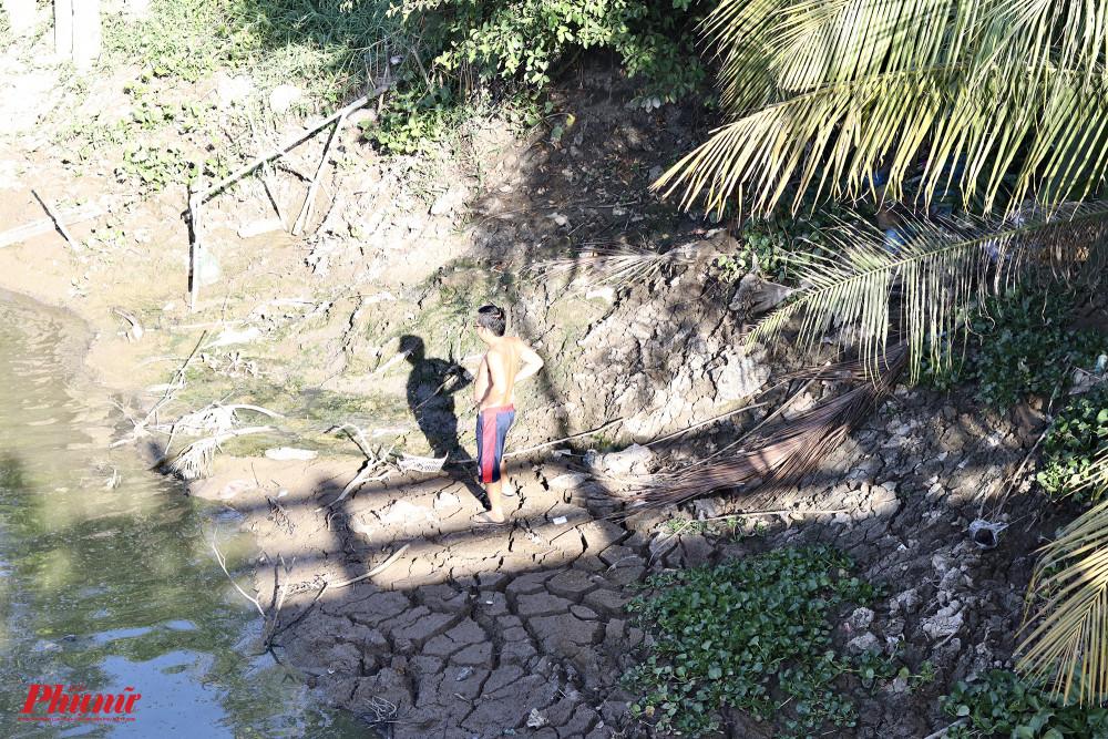 Đất dưới lòng sông khô cứng lại, nứt nẻ. Người ta có thể đi bộ dưới sông.