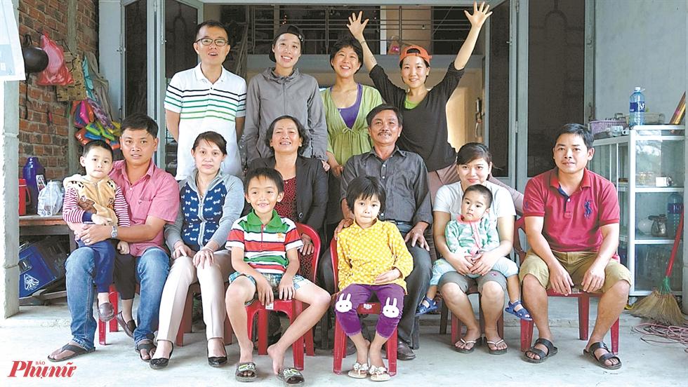 Đạo diễn Lee-Kil, thứ hai từ trái sang hàng thứ ba, chụp ảnh với Nguyễn Thị Thành, thứ tư từ hàng thứ hai bên trái, đoàn quay phim và gia đình của Nguyễn trước nhà Nguyễn ở làng Phong Nhi, Việt Nam, vào ngày 4 tháng 3 năm 2016