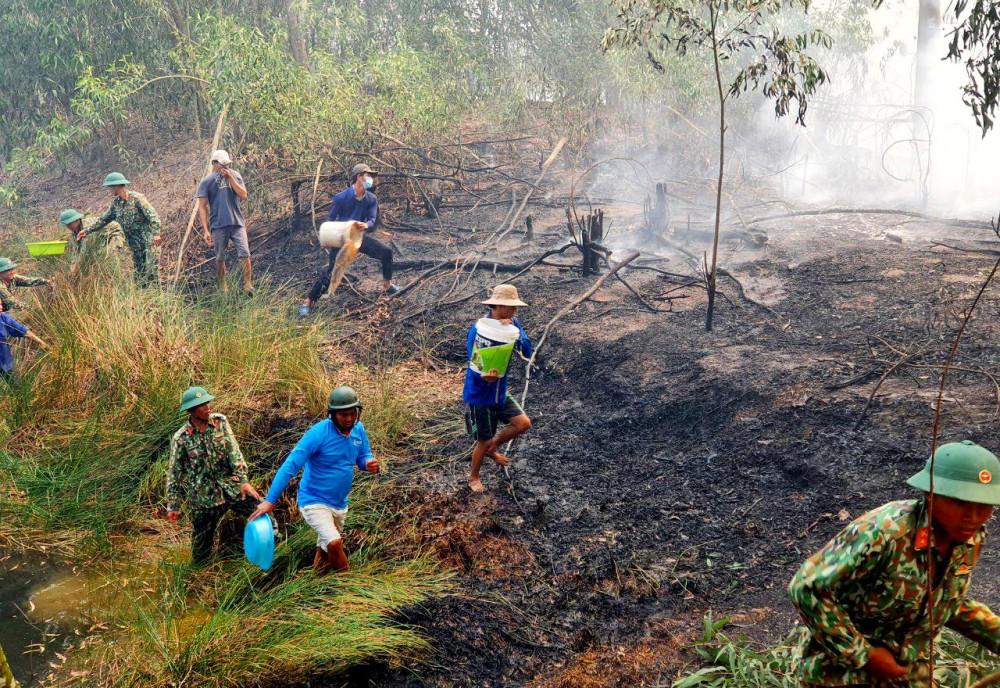 Cán bộ, chiến sỹ Tiểu đoàn bộ binh 519 phối hợp với các lực lượng địa phương và bà con nhân dân tham gia chữa cháy khu rừng tràm