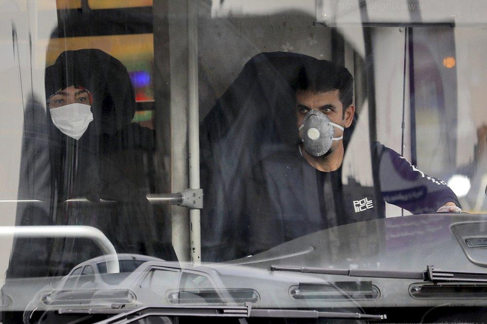 Tài xế và hành khách xe buýt đeo khẩu trang ở Iran. Ảnh: AP