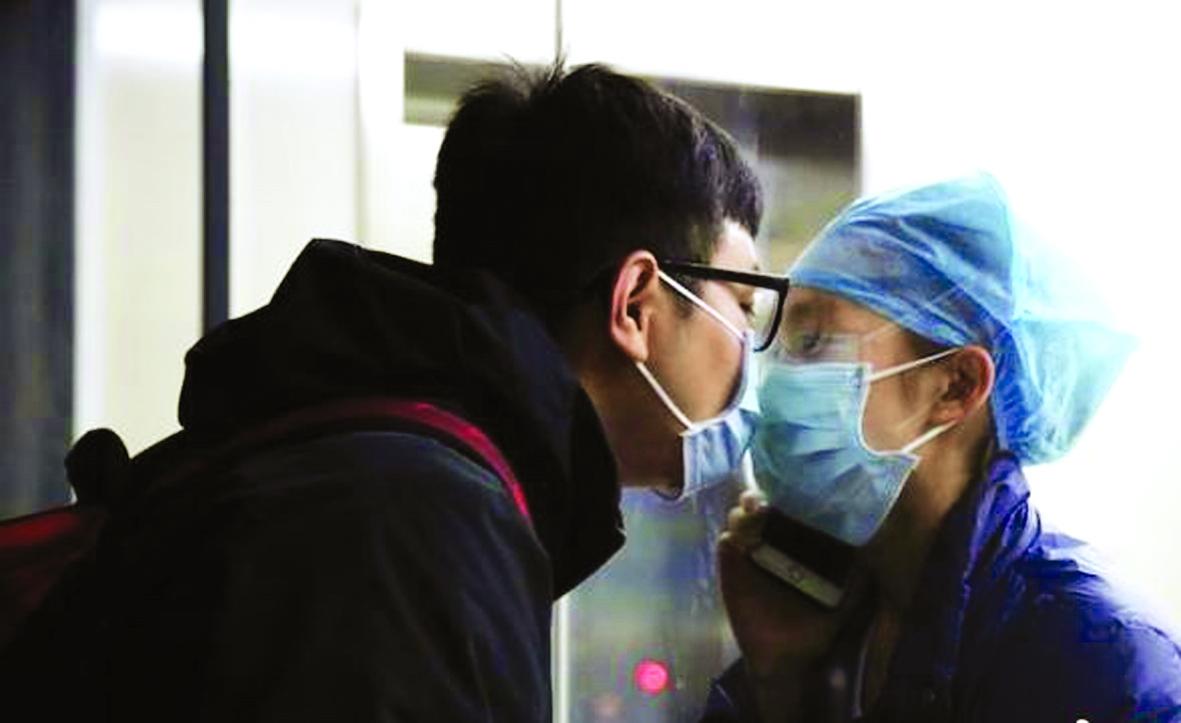 Một nữ y tá trẻ tại tỉnh Chiết Giang gặp lại chồng sắp cưới sau 11 ngày làm việc. Họ dự định kết hôn vào ngày 14/2 nhưng phải hoãn lại. Hai người trao nhau nụ hôn qua ô cửa kính nơi bệnh viện - Ảnh: China News