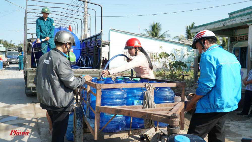 Chở nhiều thùng nước cho cả hàng xóm, người dân đã dùng xe lôi để chở nước
