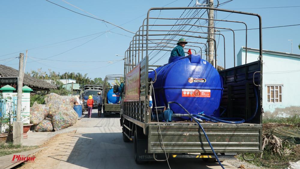 Xe cấp nước đi dọc các tuyến đường lớn, đến điểm cấp nước, người dân sẽ mang thùng ra nhận nước về sử dụng