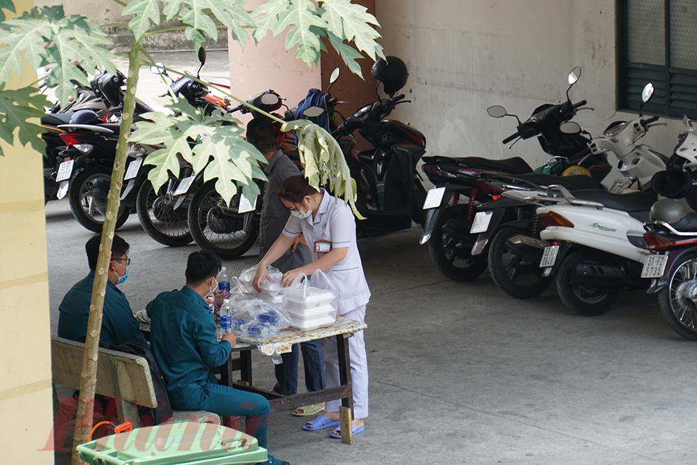 Thăm khám, dọn dẹp xong cũng gần 12g trưa, chị Thơm - điều dưỡng ở khu cách ly chạy vội xuống nhận cơm cho mọi người.