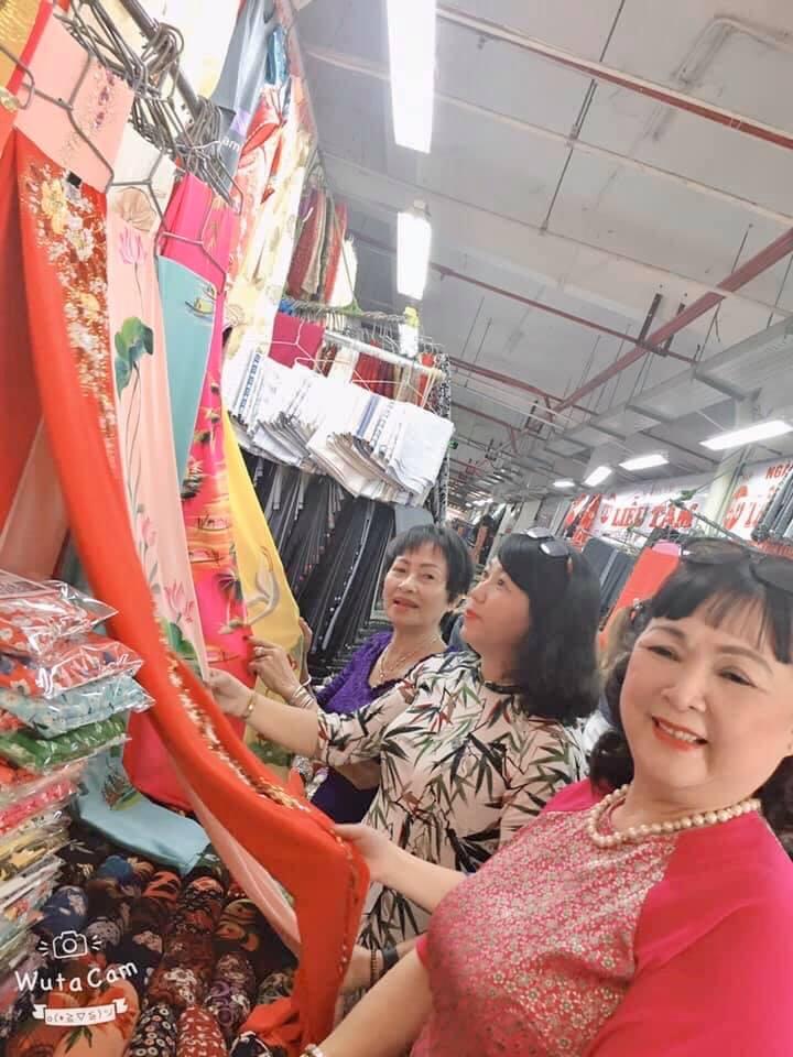 Nhiều gian hàng ở chợ Bình Tây, tiểu thương mặc áo dài, giảm giá tiền vải và công may áo dài cho hội viên