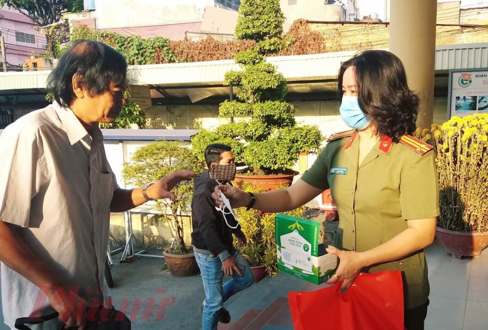 Phụ nữ công an quận tặng khẩu trang y tế cho người dân khi đến trụ sở