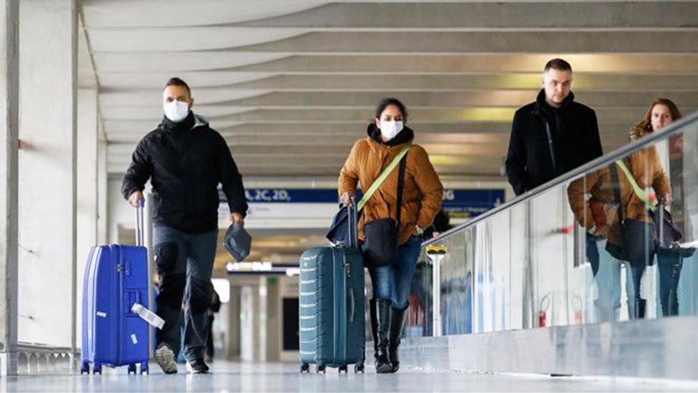 Hành khách đeo khẩu trang tại sân bay Charles de Gaulle, Pháp - Ảnh: Reuters