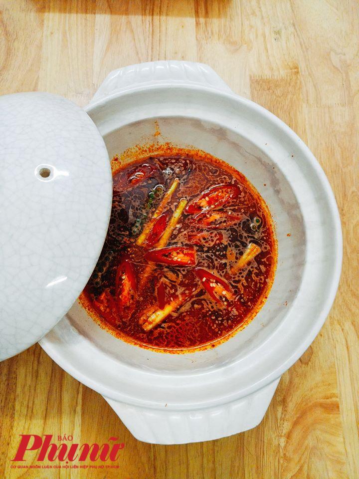 Nước lẩu sau khi hầm từ xương cá, lọc ra đem nêm nếm gia vị, sa tế vào.