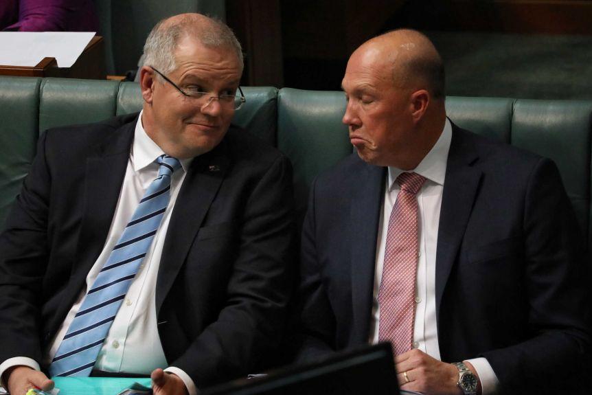 Thủ tướng Úc Scott Morrison (trái) không có tiếp xúc trực tiếp với Bộ trưởng Nội vụ Dutton (phải), trong vòng 24 giờ trước khi ông Dutton thể hiện triệu chứng nên không nằm trong diện cần cách ly.