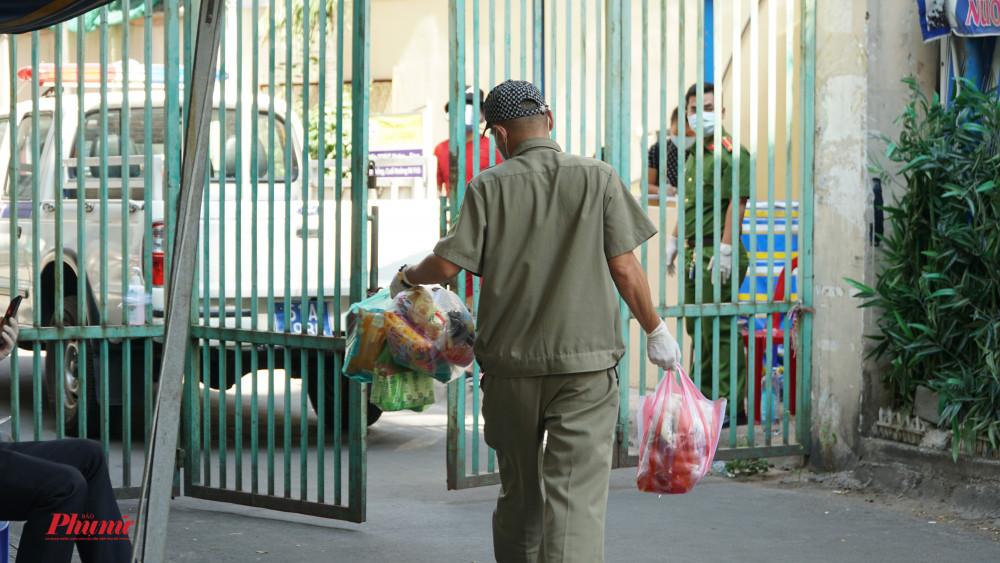 Lực lượng chức năng tích cực giúp người dân vận chuyển nhu yếu phẩm vào bên trong chung cư