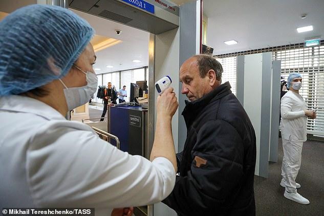 Nhân viên y tế kiểm tra nhiệt độ các khách mời trước một cuộc họp tại Moscow hôm 14/3.