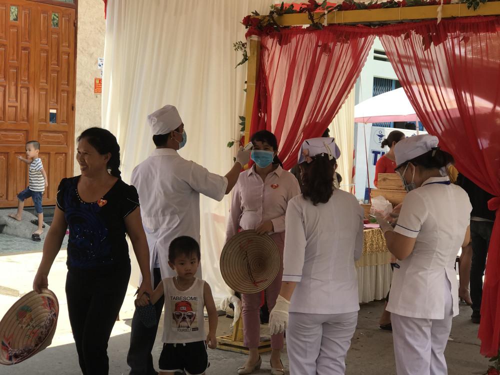 Nhân viên đo thân nhiệt cho khách mời tại đám cưới