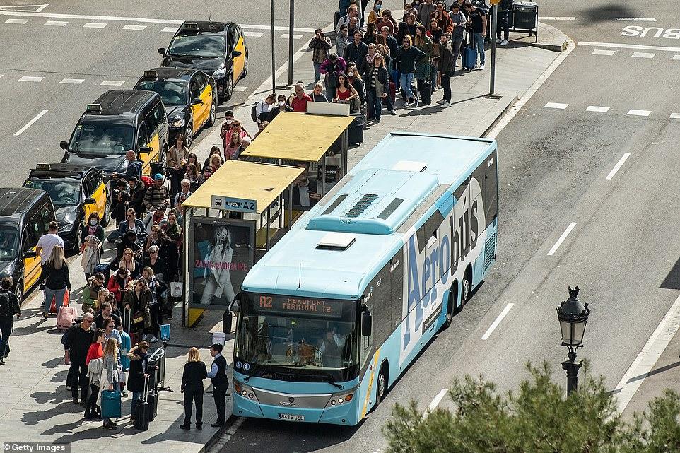 Các du khách xếp hàng chờ lên xe buýt ra sân bay tại Barcelona, hôm 15/3.