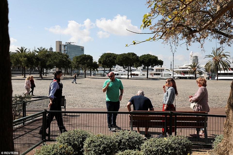 Nhân viên cảnh sát yêu cầu du khách rời đi khỏi một công viên ở khu vực Barceloneta, Barcelona.