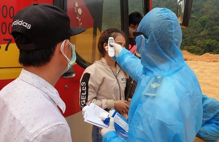 Lực lượng chức năng đang kiểm tra thân nhiệt 45 hành khách và phun thuốc khử trùng trước lúc đưa về cách ly tại đã khám sàng lọc 45 người trên xe, sau đó đưa những người chưa có biểu hiện sốt, ho về cách ly tập trung tại Tiểu đoàn 44