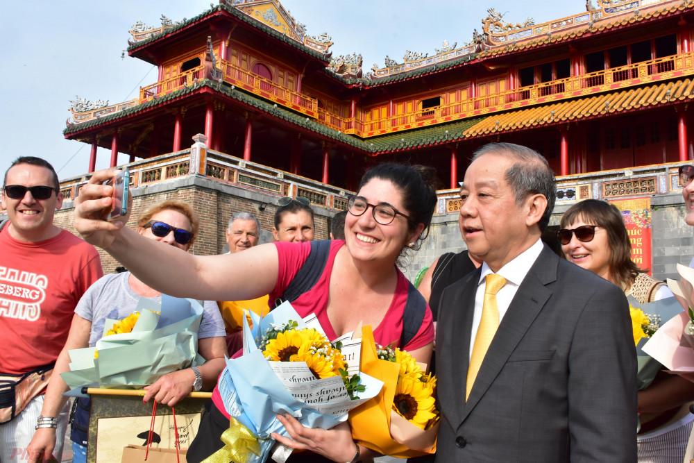 Du khách chụp ảnh kỷ niệm cùng ông Phan Ngọc Thọ trong ngày đầu năm mới  2020  tham gian Đại Nội