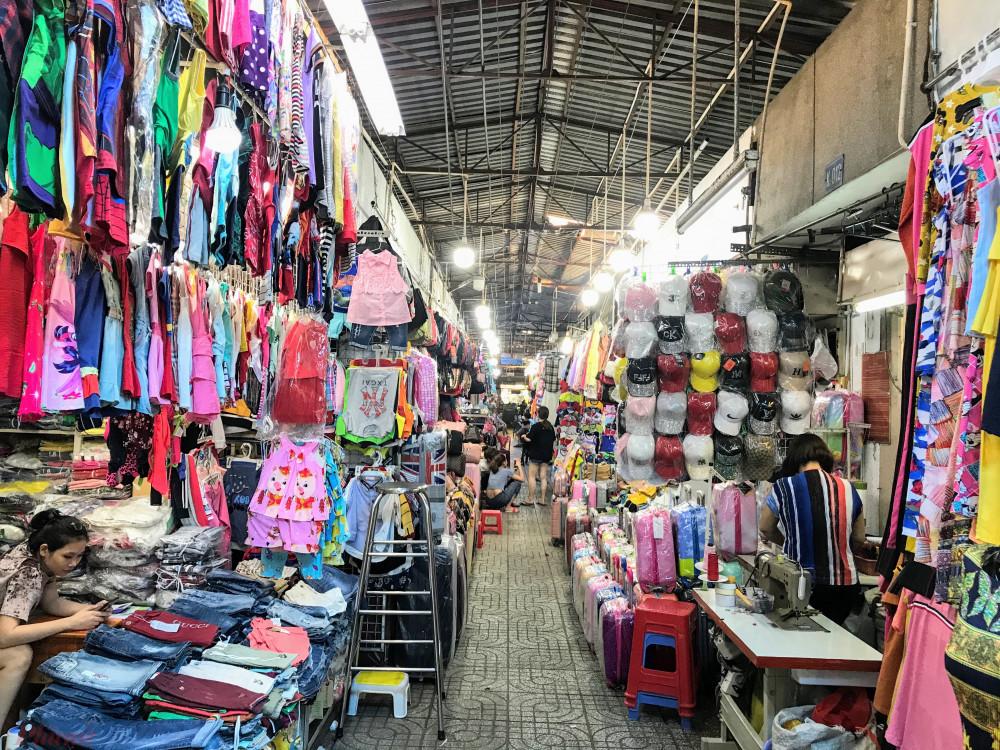 """Theo chủ cửa hàng kinh doanh quần áo nữ Chín Nghĩa, tiểu thương kinh doanh bên trong chợ Phạm Văn Hai cho hay, bà nghỉ bán mấy ngày nay, nhưng mà vì ở nhà buồn quá nên ra mở sạp treo hàng lên với mong muốn có một vài khách mua hàng cũng gỡ gạt lại phần nào vốn nằm """"chết"""" tại sạp."""