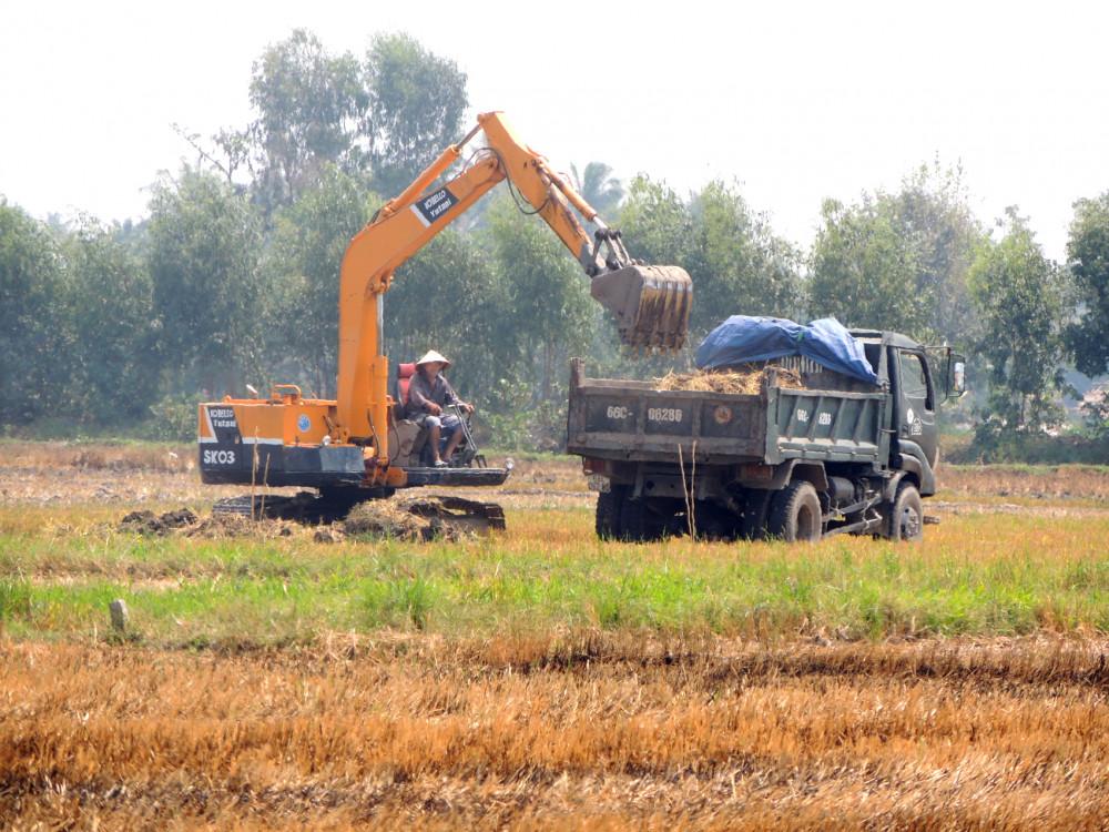 Các phương tiện xe cơ giới được huy động đến ruộng sâu để thu gom đất mặt