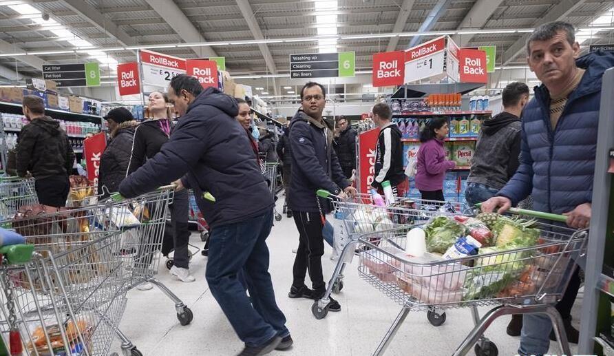 Người dân náo loạn, chen chúc nhau trong một siêu thị. Tính đến sáng 19/3, Anh ghi nhận 71 người chết và 2.626 bệnh nhân dương tính SARS-CoV-2.