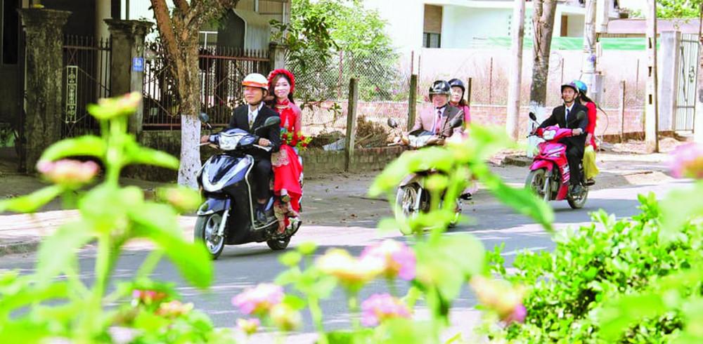 Chú rể chở cô dâu, vài người thân cũng đi xe máy theo sau, hệt một đám cưới của thập niên 1980,1990