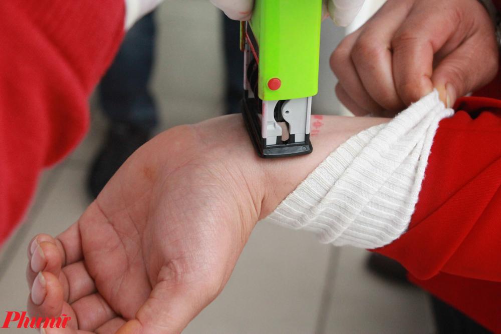 Sau khi tiến hành kiểm tra sức khỏe, sàng lọc các biểu hiện bệnh, người đến khám được đóng dấu theo ngày để không để lọt trường hợp nghi nhiễm.