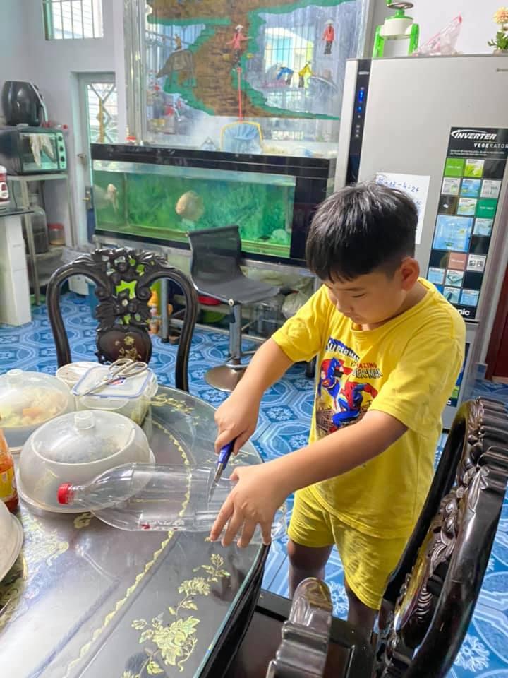 Nguyễn Đặng Gia Phúc đang thực hiện làm đồ đựng điện thoia5 và ống cắm bút từ chai nhựa đã qua sử dụng.
