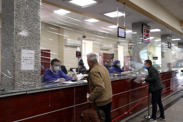 Một bức màn chắn bằng nhựa được dựng lên tại khu vực giao dịch của một ngân hàng tại Iran nhằm tránh sự tiếp xúc trực tiếp giữa nhân viên và khách hàng.