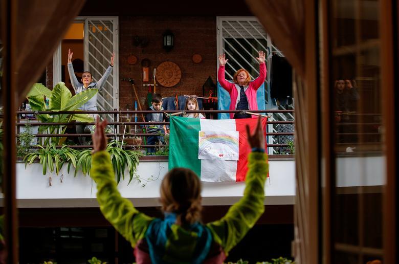 Huấn luyện viên cá nhân Antonietta Orsini tổ chức một lớp tập thể dục cho hàng xóm của mình từ ban công trong khi bị khóa ở Rome, Ý, ngày 18 tháng 3