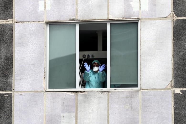 Một nhân viên y tế tại Madrid, Tây Ban Nha vẫy chào mọi người từ cửa sổ bệnh viện.