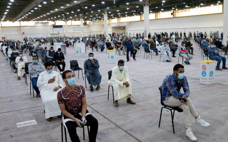 Người nước ngoài chờ xét nghiệm y tế bắt buộc tại Kuwait vào ngày 14/3. Họ được xếp ngồi xa nhau, trên những hàng ghế đã được tình nguyện viên sắp sẵn.