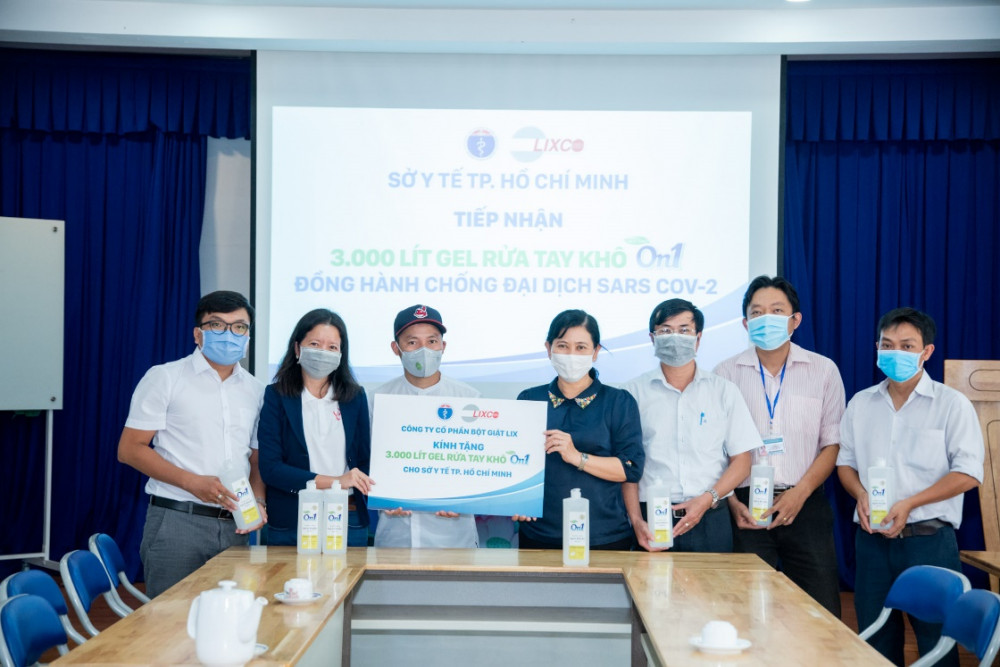 Đại diện LIXCO và rapper Đinh Tiến Đạt trao tặng 3.000l gel rửa tay khô cho Sở Y tế TP.HCM. Ảnh do LIXCO cung cấp