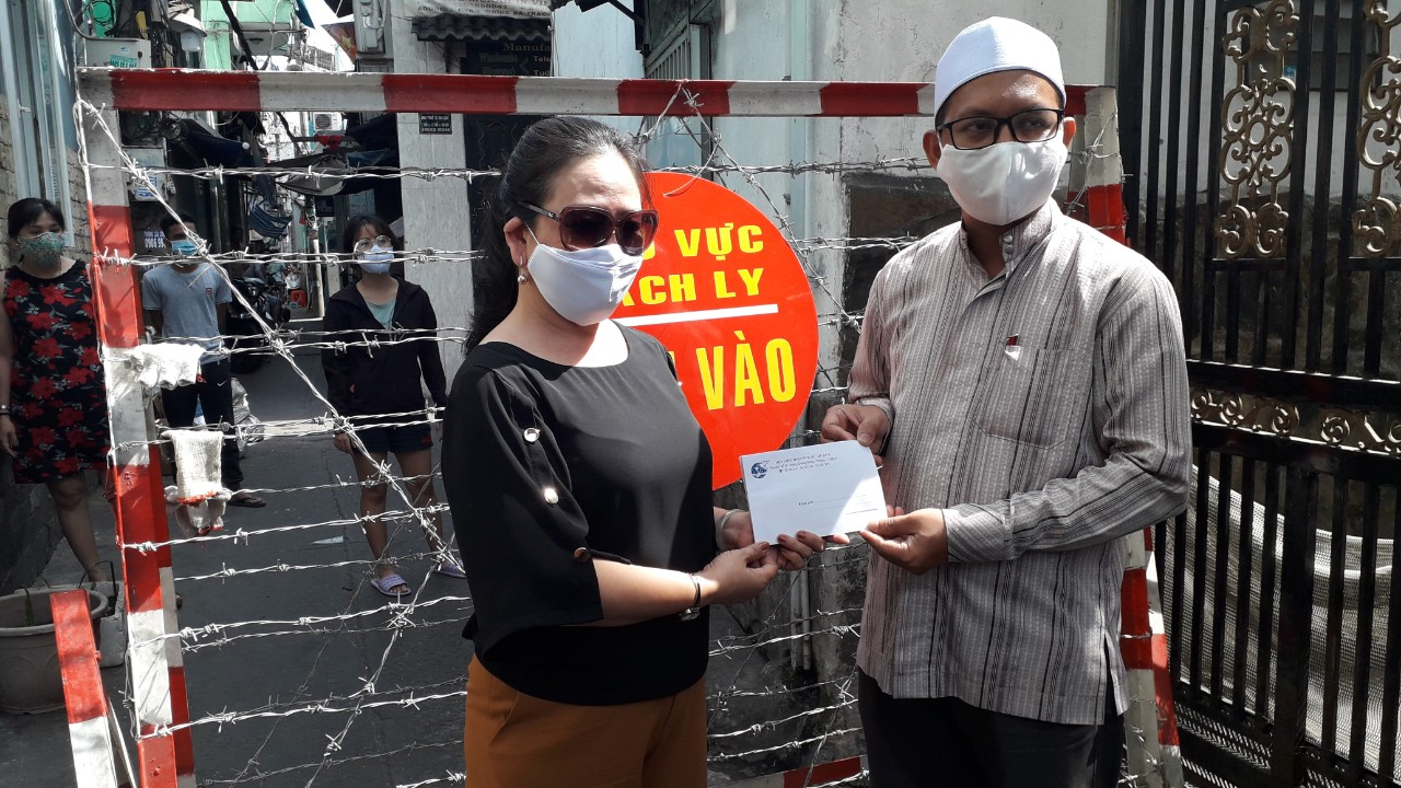 Bà Quách Thị Kim Phượng - Chủ tịch Hội LHPN Q8 (bên trái) trao tiền hỗ trợ những người phục vụ khu vực cách ly cộng đồng hội giáo khu vực cách ly.