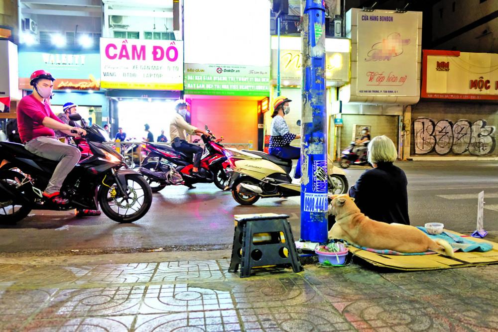 Người phụ nữ bán vé số và chú chó tên Bé ở góc đường Hai Bà Trưng, Q.3 ẢNH: ĐẬU DUNG