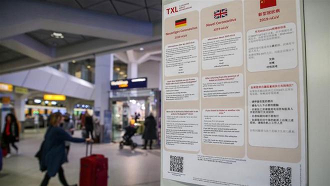 Thông tin về dịch COVID-19 bằng 3 ngôn ngữ Đức, Anh và tiếng Hoa tại sân bay Tegel ở Berlin, Đức AFP