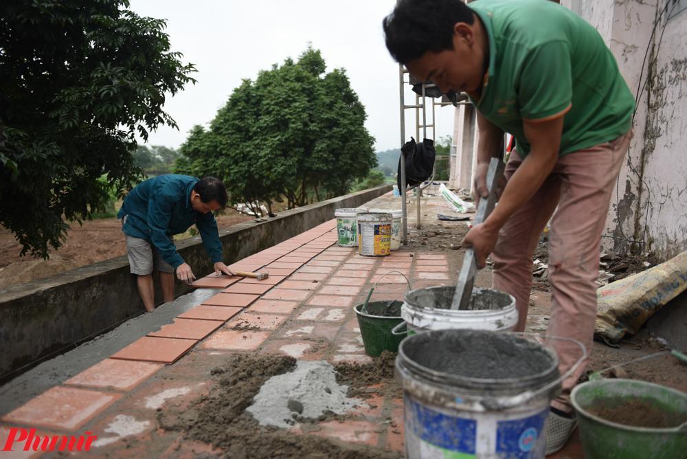 Các công nhân tiến hành lát lại nền gạch mới cho bệnh viện.