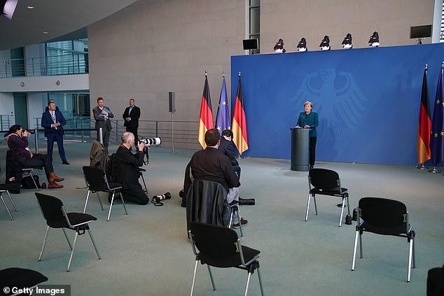 CÁc phóng viên và nhân viên giữ tuân thủ khoảng cách quy định trong một buổi họp báo của bà Merkel.