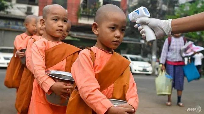 Đo nhiệt độ các chú tiểu ở Yangon. Ảnh: AFP