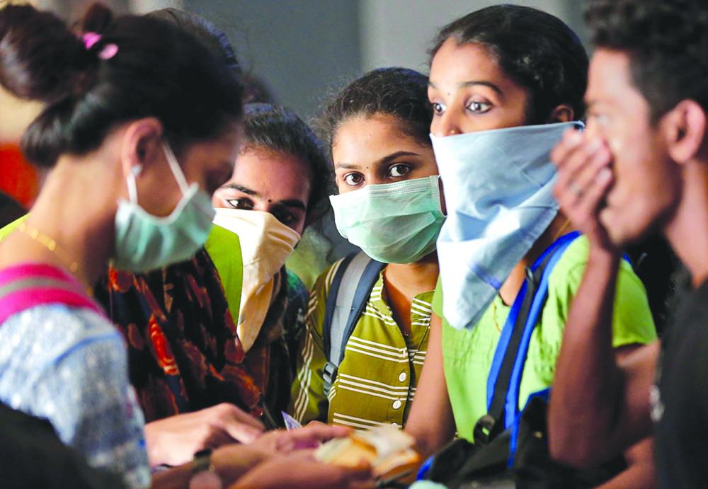 Một nhóm sinh viên đeo khẩu trang chờ mua vé ở ga xe lửa tại Kochi, Ấn Độ - Ảnh: Reuters