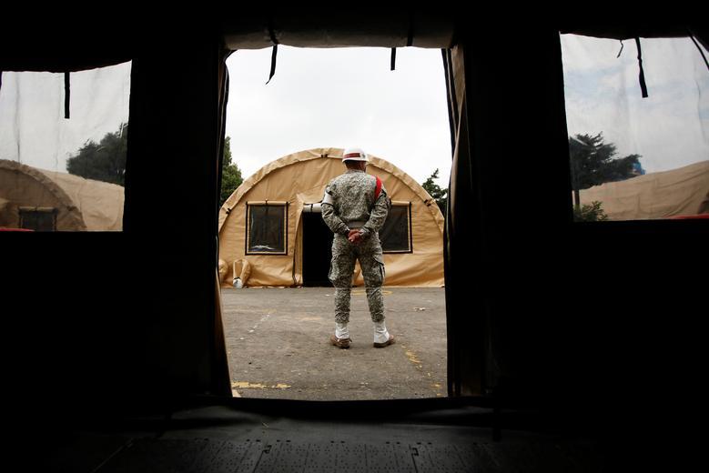 Một người lính đang canh giữ những căn lều đang được dựng trong bãi đậu xe của Bệnh viện Quân đội ở Bogota, Colombia