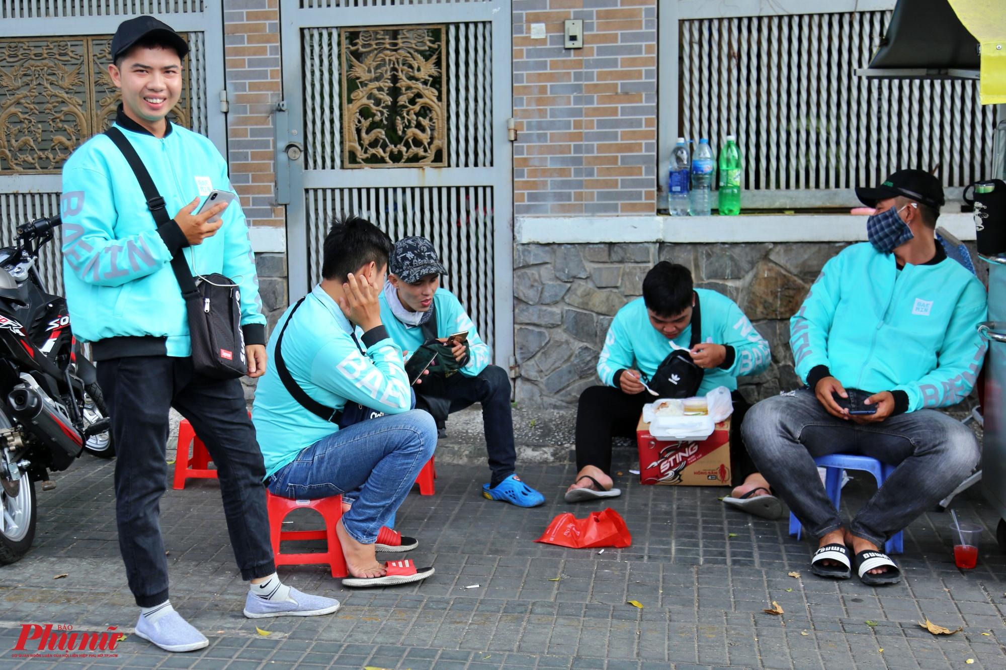 Một nhóm nhân viên giao hàng Baemin tranh thủ ngồi nghỉ trưa trước nhận các đơn hàng của khách ship vào chiều một, một số anh em chia sẻ đa số khách thường đặt thức ăn vào buổi trưa và buổi tối là nhiều nhất