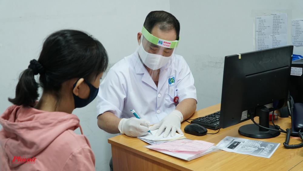 Bác sĩ Minh Huy đeo mặt nạ khi thăm khám cho bênh nhân