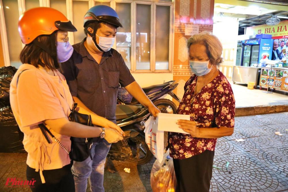 """Một cụ bà nhặt ve chai trên đường Nguyễn Thị Minh Khai bất ngờ nhận được món quà của Báo Phụ Nữ. Hỏi về công việc của mình, bà nói: """"Dịch bệnh, hàng quán đóng cửa hết rồi nên tối này chẳng nhận được gì cả""""."""