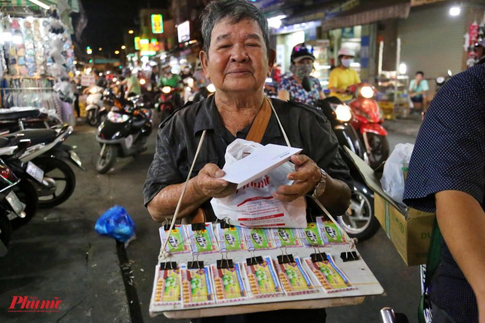 Người đàn ông bán vé số ở chợ Thị Nghè vui mừng khi nhận được phần quà của Báo Phụ Nữ. Ông cho biết, mấy hôm nay mình không có khẩu trang đeo, nay được tặng sẽ rửa tay sát khuẩn và đeo khẩu trang nghiêm chỉnh.