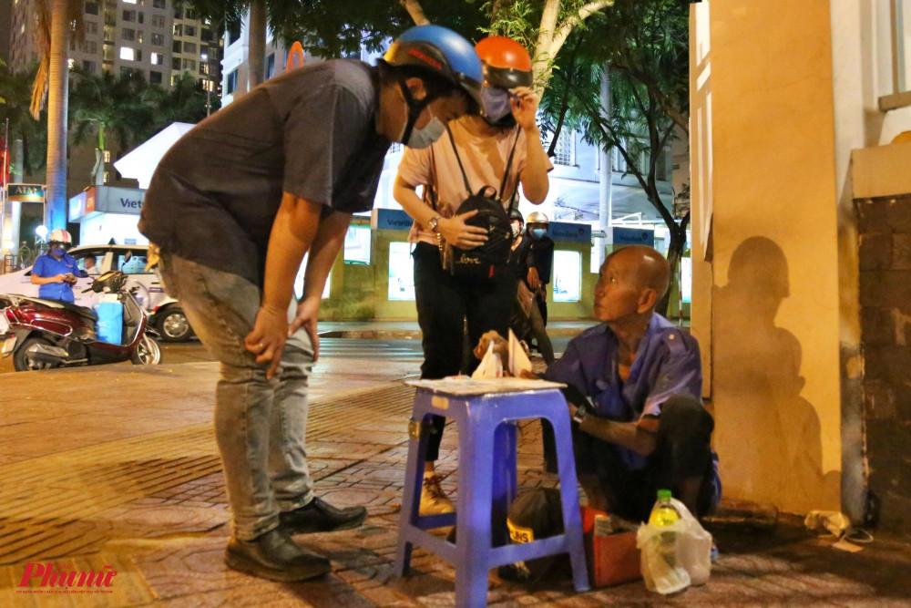 """Dịch bệnh tràn về khiến người lao động ở vỉa hè, người vô gia cư lao đao vì mất thu nhập. Người đàn ông bán vé số trong ảnh cho biết: """"Dịch bệnh người ta ít ra đường, tôi ngồi cả buổi tối mà chỉ mới bán được mấy tờ vé số""""."""