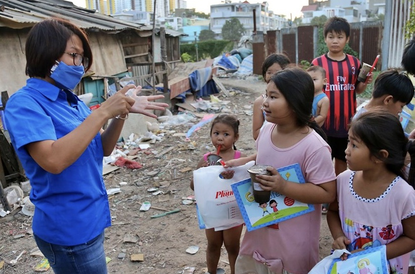 Đoàn viên Chi đoàn Báo Phụ Nữ TPHCM hướng dẫn các em nhỏ tại xóm Chùa cách đeo khẩu trang, rửa tay và tuyên truyền về các biện pháp phòng tránh dịch COVID-19.