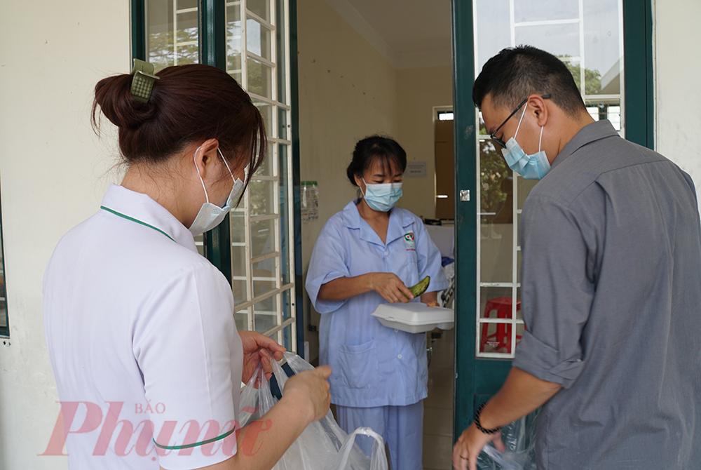 Nhân viên y tế nhận cơm, mang lên các tầng lầu cho những người đang cách ly