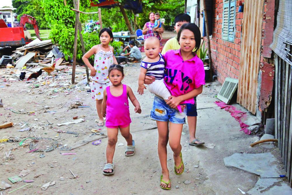 Trẻ con trong xóm Chùa hớn hở xúm xít đợi nhận quà. Ảnh Minh Trâm